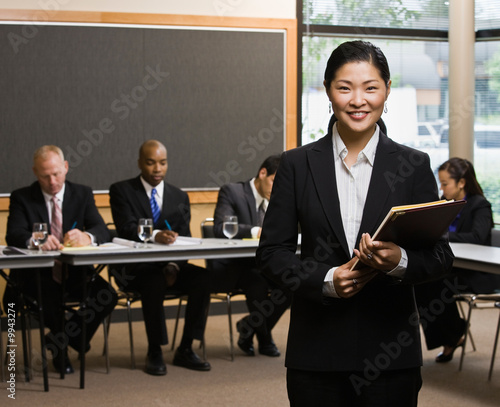 Asian businesswoman standing in front of co-workers