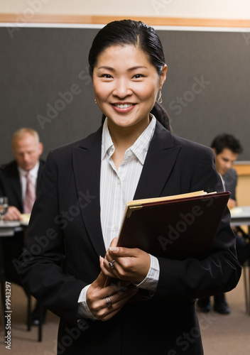 Asian businessman holding files in front of co-workers