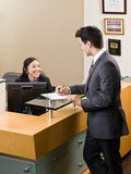 Friendly receptionist greeting man at front desk