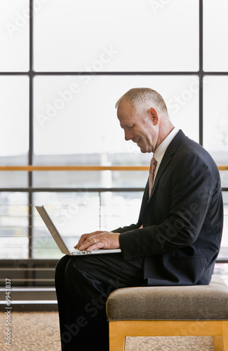 Mature businessman working on laptop in office lobby
