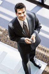Businessman with cell phone text messaging  in office lobby
