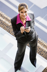 Businesswoman holding electronic organizer in office lobby