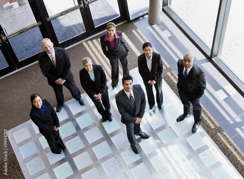 Multi-ethnic co-workers standing in office lobby
