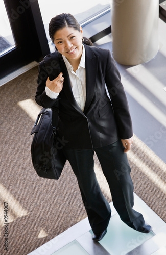 Businesswoman holding briefcase in office lobby