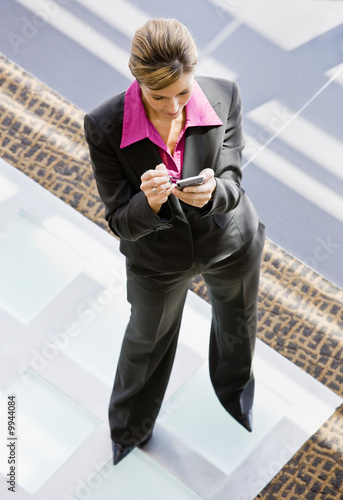 Businesswoman writing in electronic organizer in office lobby