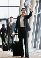 Business traveler pulling suitcase and waving to co-worker