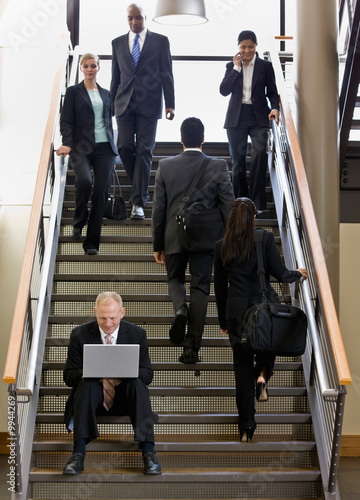 Businessman sitting and working on laptop on busy office stairs