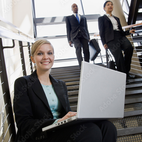 Businesswoman sitting and working on laptop on office stairs