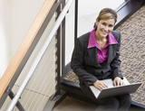 Businesswoman working on laptop on office stair landing
