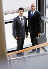 Male co-workers posing together in corner of office building