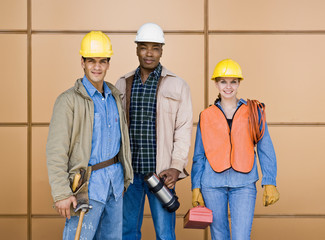 Construction workers posing in hard-hats with tools