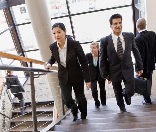 Co-workers ascending and descending office stairs