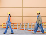 Side view of construction workers carrying ladder together