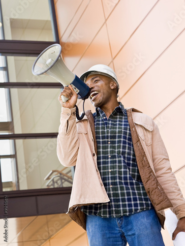 Construction worker making announcement into bullhorn