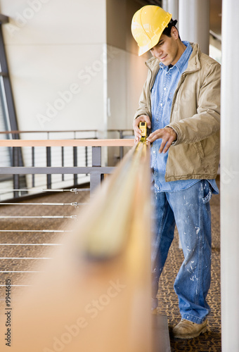 Construction worker taking measurement with measuring tape
