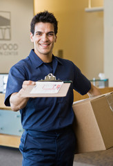 Delivery man in uniform presenting shipping receipt