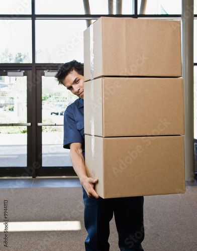 Delivery man in uniform carefully carrying stack of boxes