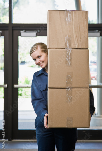 Woman in uniform carefully carrying stack of cardboard boxes