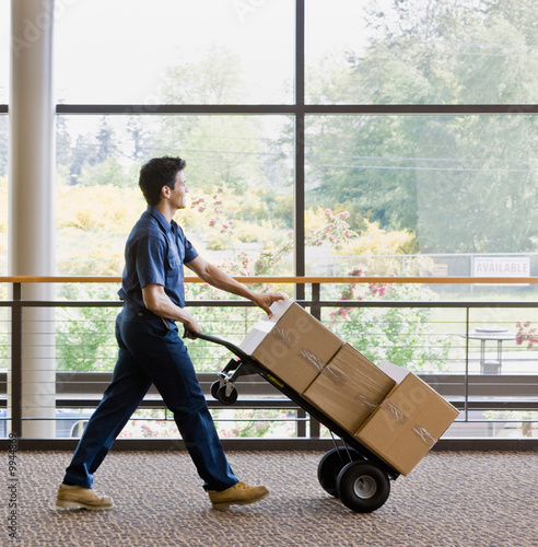 Delivery man in uniform pushing stack of boxes on dolly