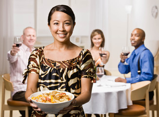 Hostess serving bowl of pasta to guests at dinner party