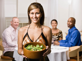 Hostess serving bowl of salad to guests at dinner party