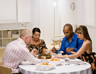 Couples holding hands and praying before elegant dinner party