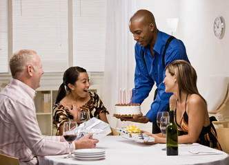 Host serving birthday cake to surprised wife at dinner party