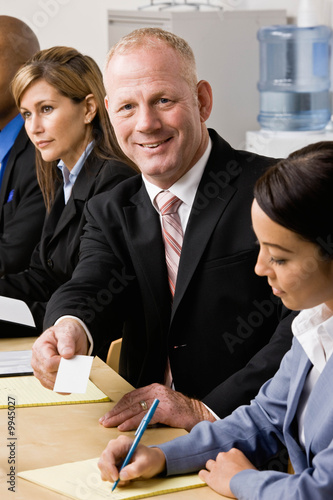 Confident businessman handing co-worker business card in meeting