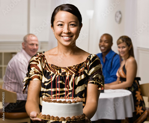 Hostess serving birthday cake to guests at dinner party