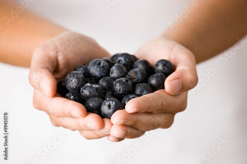 Man holding handful of wholesome, fresh blueberries