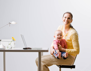 Working mother holding baby with laptop on desk