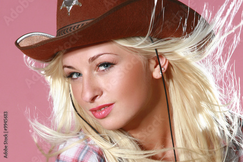 Sexy woman with cowboy hat on pink background