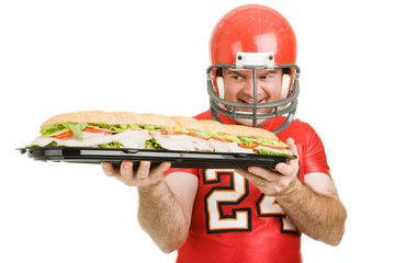 Football player hungrily looking at a giant sub sandwich.