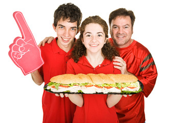 Sports fans getting ready to chow down on a giant sandwich.