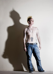 Punk with tattoos leaning against a white wall