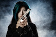 Asian beauty holding gun with smoke in background