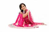 Fototapety Beautiful Bangali bride in colorful dress sitting, isolated