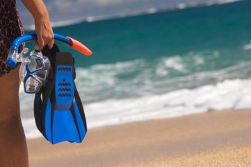 Woman Holding Snorkeling Gear on the shoreline.