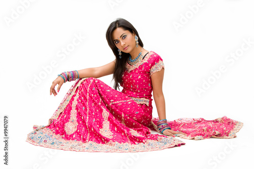 Beautiful Bangali bride in colorful dress sitting, isolated