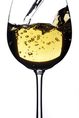 White Wine being poured in a wine glass; isolated