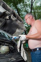 Man mechanic repairing his car on the road