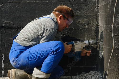 Construction worker making a culvert in foundation wall