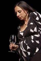 schwangere Frau schaut ernst auf leeres Weinglas