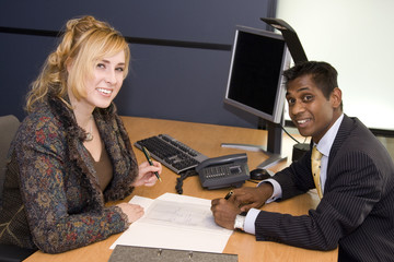 Indian Business Man and Caucasian Woman Signing a Contract