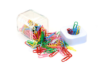 Colorful paperclips spilled from cup on white