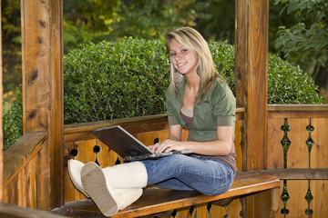 A beautiful blond teenage girl using her laptop in the park