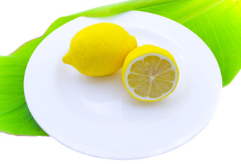 Whole and a lemon half on a white plate