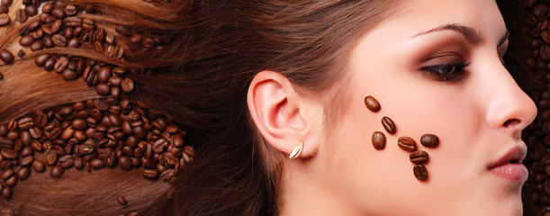 coffee beans on the hair and face of beautiful young woman