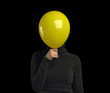A yellow balloon over a persons face