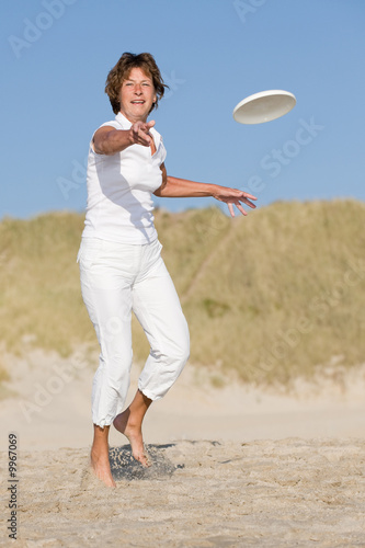 Active senior woman is tossing a frisbee at the beach
